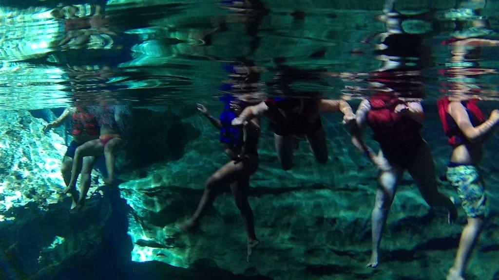 pessoas fazendo flutuação no poço azul